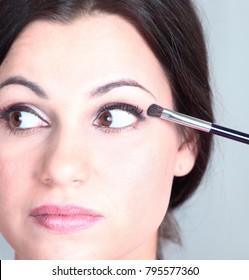 closeup . beautiful woman with brush for makeup