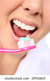 A close-up of a beautiful woman brushing her teeth