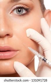 closeup beautiful woman face, syringe injection to nasolabial fold  beauty concept