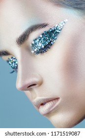 Close-up of a beautiful woman with fashion makeup against a blue background