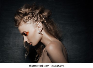 close-up of beautiful woman in fashion pose, braid hairstyle, stylish fashion earings  and creative orange smoky eyes