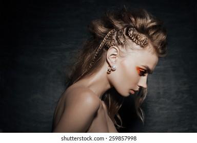close-up of beautiful woman in fashion pose, braid hairstyle, stylish fashion earings  and creative orange smoky eyes