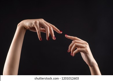 Closeup of beautiful woman hands with red manicure on the nails. Cream for palms, manicure and beauty treatment. Elegant and graceful arms with slender graceful fingers. Copy space. Isolated on black.