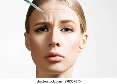 Close-up of a beautiful woman making botox injection on white background