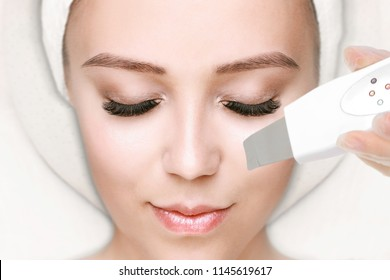 Close-up Of Beautiful Woman Receiving Ultrasound Cavitation Facial Peeling. Ultrasonic Skin Cleansing Procedure. Beauty Treatment. Beauty, spa, cosmetology and skincare concept. Cosmetological clinic.