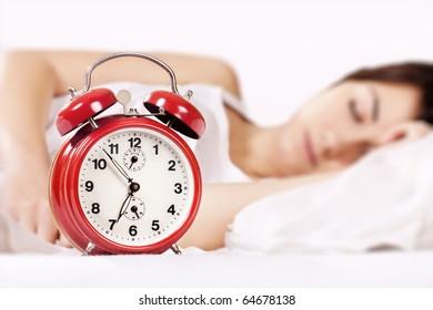 Closeup of beautiful woman sleeping and alarm clock (focus on alarm clock).