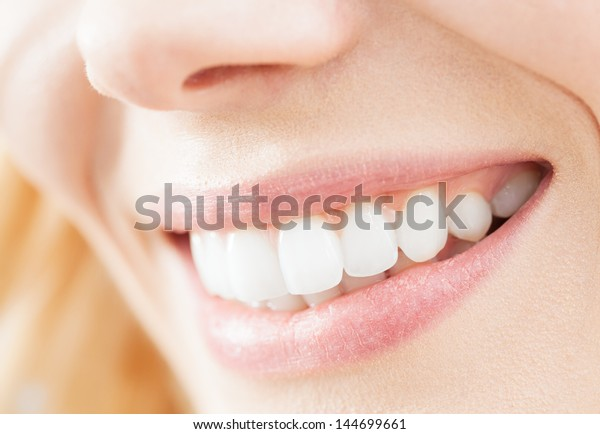 A close-up of a beautiful woman smile.