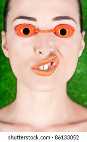 Closeup of a beautiful woman wearing tanning bed glasses and pulling a strange face isolated on green