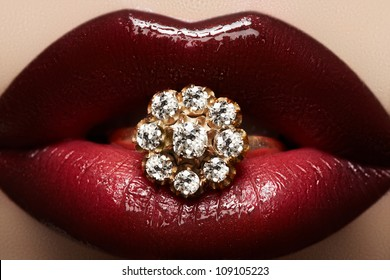 Close-up of beautiful woman's lips with bright fashion dark red glossy makeup. Macro lipgloss cherry make-up. Mouth with wedding gold diamond ring. Jewelry accessories.