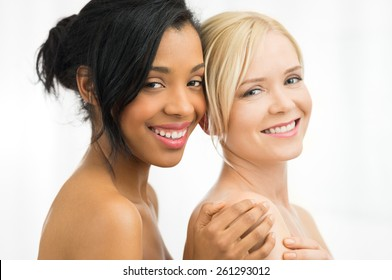 Closeup of beautiful young african and caucasian woman looking at camera  isolated on white background