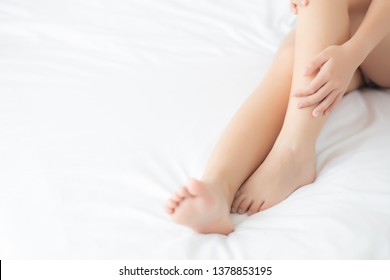 Closeup beautiful young asian woman sitting on a bed stroking legs with soft smooth skin in the bedroom, girl applying body cream and lotion with treatment care, healthy and wellness concept.