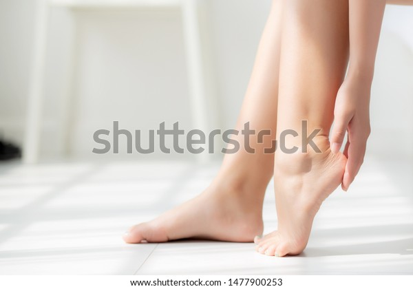 Closeup beautiful young asian woman applying cream and lotion onto foot dry on bed, beauty asia girl moisturizer and treatment cosmetic onto toes and heel, skincare cosmetic and healthy concept.