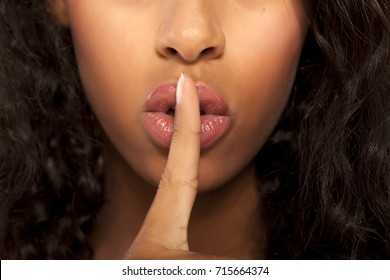Closeup of a beautiful young dark-skinned woman with finger on her lips on a white background. Concept for silence