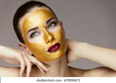Closeup Of Beautiful Young Female Model With Gold Mask Caressing Face With Hands.