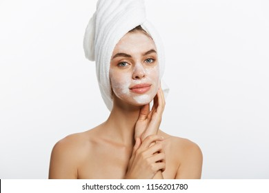 close-up of beautiful young woman applying cream with bath towel on head