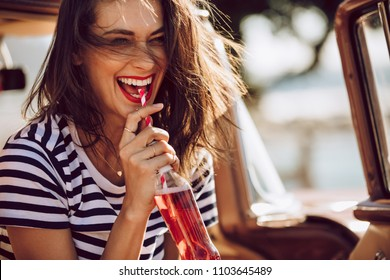 Closeup of beautiful young woman enjoying drinking cola with straw while sitting in a car. Female on a road trip having soft drink.