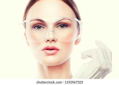 Close-up beautiful young woman face with perfect clean skin, rose lips, nude make-up wearing doctor uniform. Beautician or nurse health care concept. Toned image