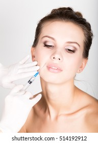 Closeup of Beautiful young woman gets injection in eye and lips area from beautician. preservation of beauty concept