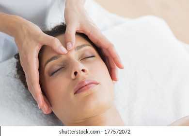 Closeup of beautiful young woman having head massage in health spa