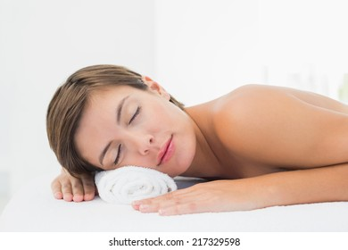 Close-up of a beautiful young woman lying on massage table at spa center