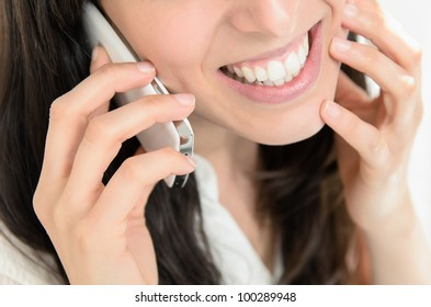 Close-up of a beautiful young woman talking on mobile phone intimately and smiling