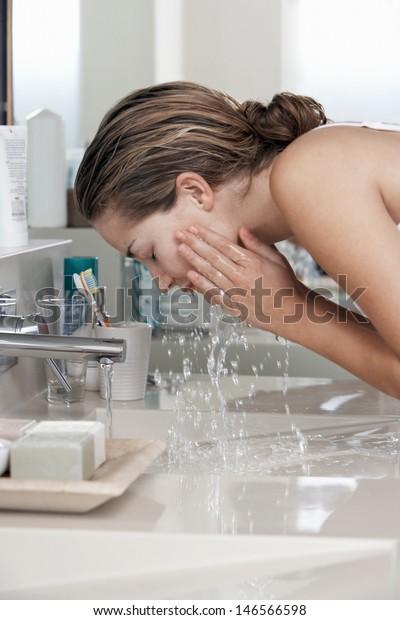 浴室で顔を洗う美しい若い女性の接写
