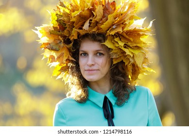 Closeup of beautiful young woman wearing  wreath of golden maple leaves.