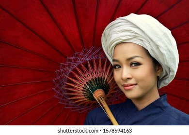 Closeup beautiful young woman wearing traditional dress with turban smiling on red umbrella background.