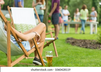 Close-up of beautiful young woman's legs, girl enjoying summer vacation, relaxing while sitting on deck chair with beer, friends at garden party in the background