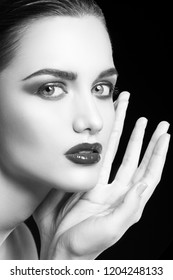 Close-up beauty face of young beautiful girl model with glossy lips make-up, smokey eye shadows, clean skin touching chin, on black background. Skincare facial treatment concept. Black and white