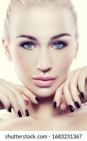 Close-up beauty face of young modern woman with nude makeup, healthy perfect skin, blue eyes, hands near face, black nail manicure