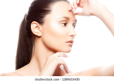 Close-up beauty face of young woman with perfect skin, hand near cheek, natural nude make-up, brunette hairstyle. Facial treatment spa female health concept. Isolated. White background