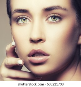 Closeup beauty face of young woman model with natural skin makeup, lips, green eyes holding hand near cheek