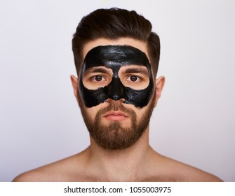 Closeup beauty image of Young man with black mask on the face isolated on gray background