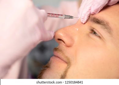 Closeup Of Beauty master Doing Injection In Young Male Patient Face. Man receiving Beauty Procedure Using Filler Injections. Cosmetology And Beauty Concept of facial Injection.