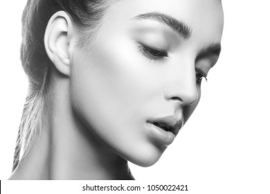 Closeup beauty model girl face. Natural lips, nude make-up, clean skin. Facial treatment concept. White background. Black and white
