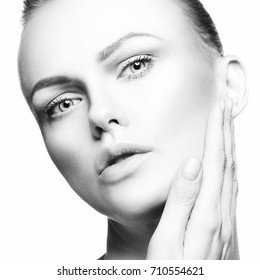 Close-up beauty model woman face with hand on cheek. Natural make-up, perfect skin. Skincare health concept. White background. Black and white