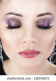Closeup beauty portrait of attractive model face with bright visage. Violet eye makeup and pink lips make-up. Evening style.