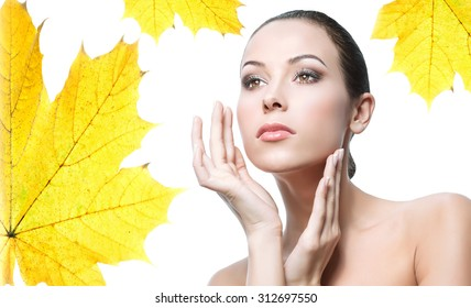 closeup beauty portrait of attractive young caucasian woman brunette isolated on white studio shot lips  face hair head and shoulders hands yellow maple leaf autumn
