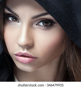 Closeup beauty portrait of attractive young woman with beautiful brown eyes. Hood on head. Brunette girl. Studio shot.
