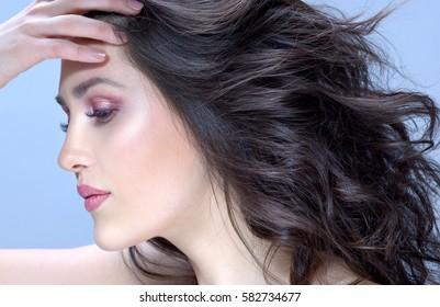 closeup beauty portrait of attractive young caucasian woman brunette on blue background  studio shot lips face hair head and shoulders  hands makeup