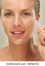 closeup beauty portrait of beautiful blonde woman peeling off a facial mask, smiling