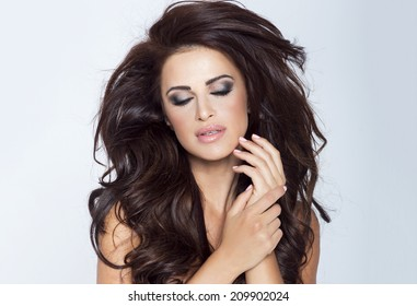 Closeup beauty portrait of beautiful brunette woman with perfect evening makeup and long curly hair. Girl with closed eyes, front view.