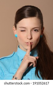 Close-up beauty portrait of woman showing silence sign and looking at camera