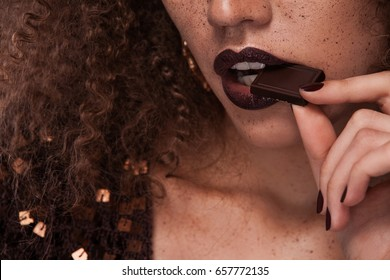 Closeup beauty portrait of young african american girl with afro hairstyle and chocolate . Girl posing on brown background, looking at camera. Studio shot.