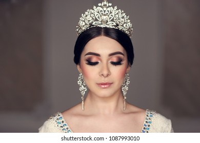 Closeup beauty portrait of young beautiful bride with hairstyle, diamond crown and earring. Brunette woman