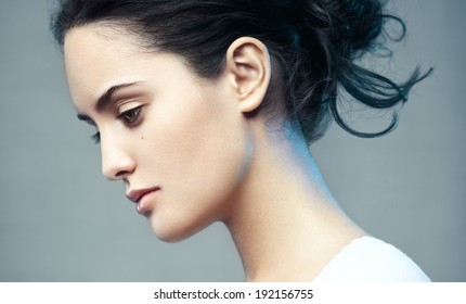 Closeup beauty portrait of a young beautiful brunette woman. Muse. Profile, looking down.
