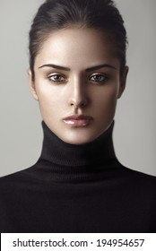 Closeup beauty portrait of a young brunette model in a black roll neck jumper. Be strong.