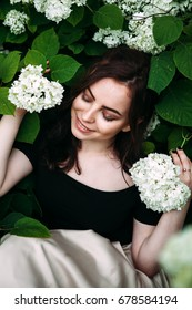 Closeup beauty portrait of young pretty happy smiling girl with dark hair posing between white hydrangeas looking down.