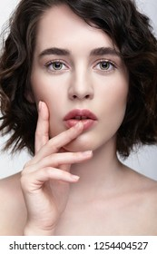Closeup beauty portrait of young woman with hands near face. Brunette girl with l day nude female face makeup.
